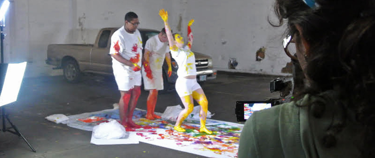 Three young people wearing white, their feet and hands covered in paint, dance across a canvas. A woman films them.